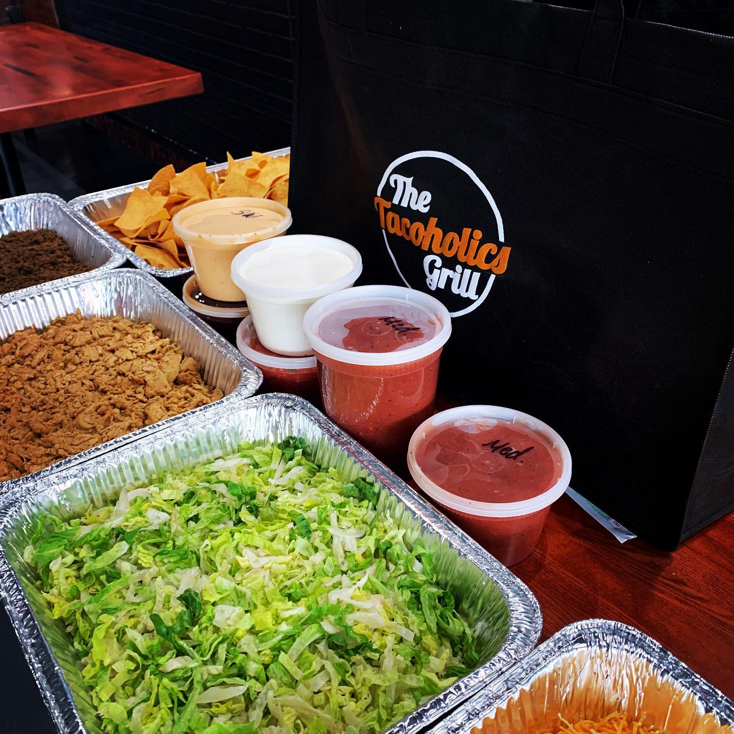 tacoholics catering including trays of beef, chicken, lettuce, chips, and jars of salsa, sour cream, and queso