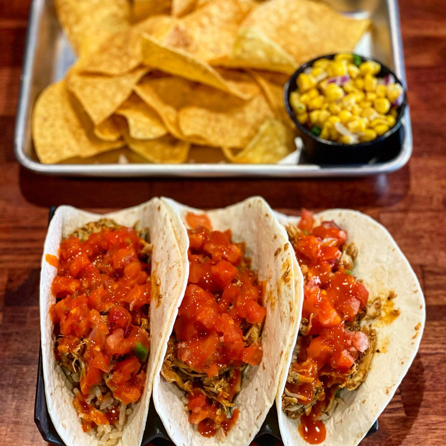 3 tacos with a side of chips and corn salsa