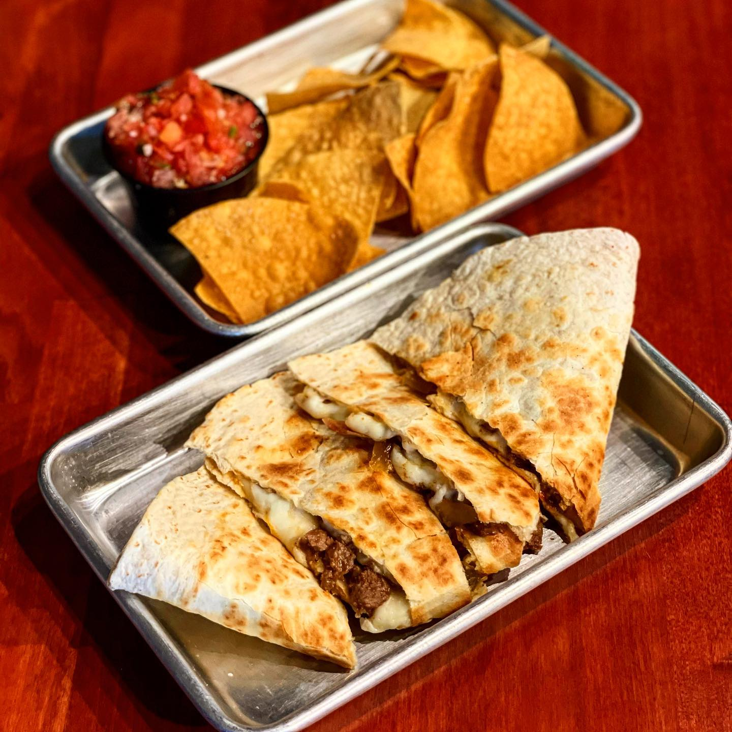 a quesadilla with chips and salsa on the side