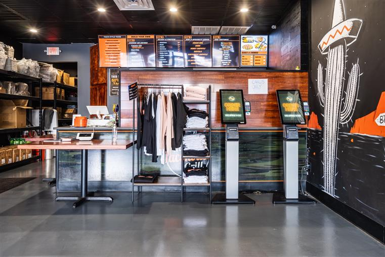 inside the brick location restaurant with apparel lined up