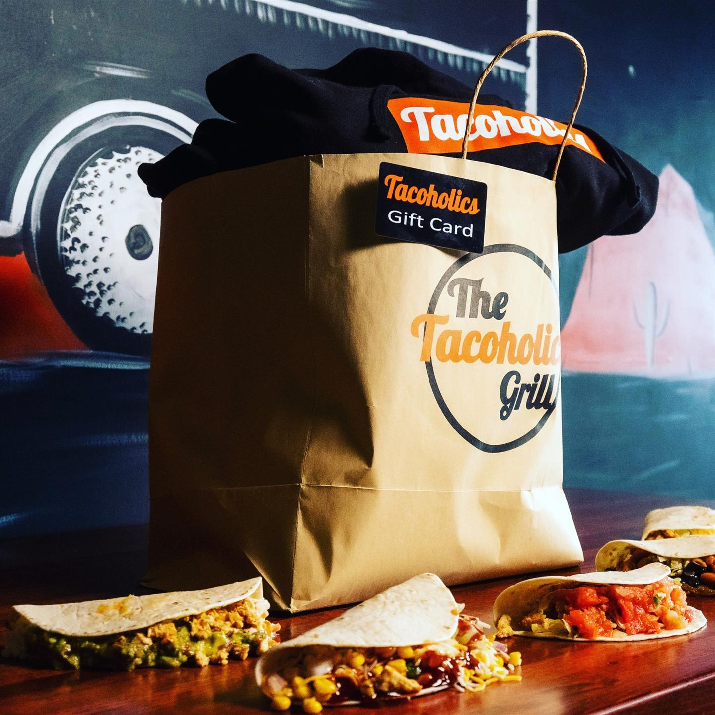 a tacoholics bag with apparel inside and tacos laying around it