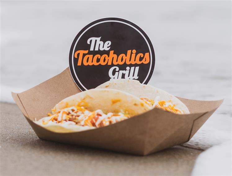 """2 tacos in a cardboard bowl with a """"the tacoholics grill"""" sign"""