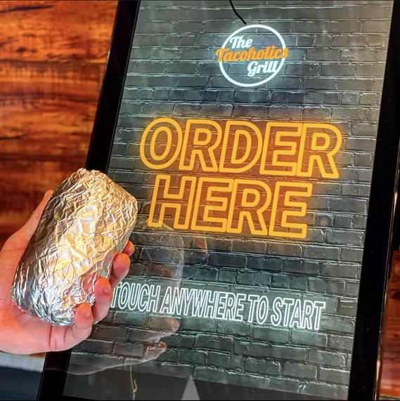 a hand holding a burrito in front of a kiosk