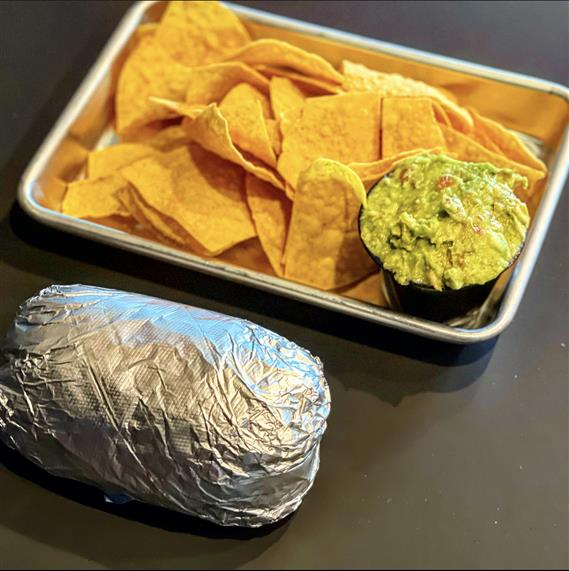 burrito wrapped in tin foil with chips and guacamole on the side