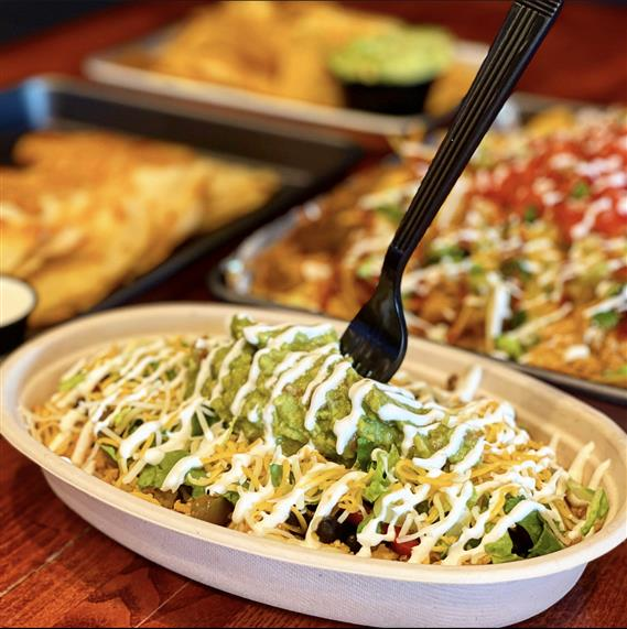 burrito bowl topped with cheese, sour cream, and guacamole