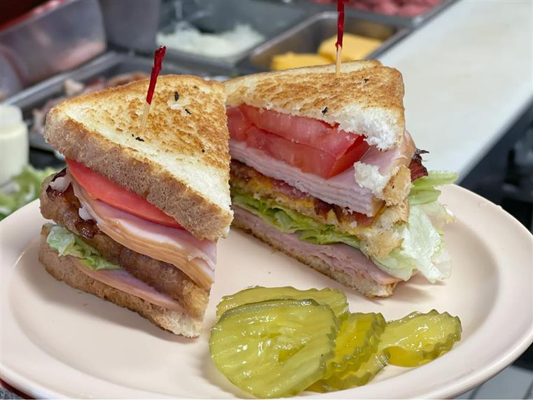 chicken club sandwich with a side of pickles