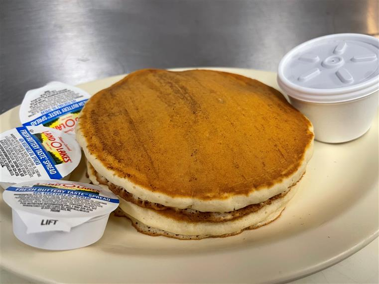 two pancakes with a side of butter and syrup