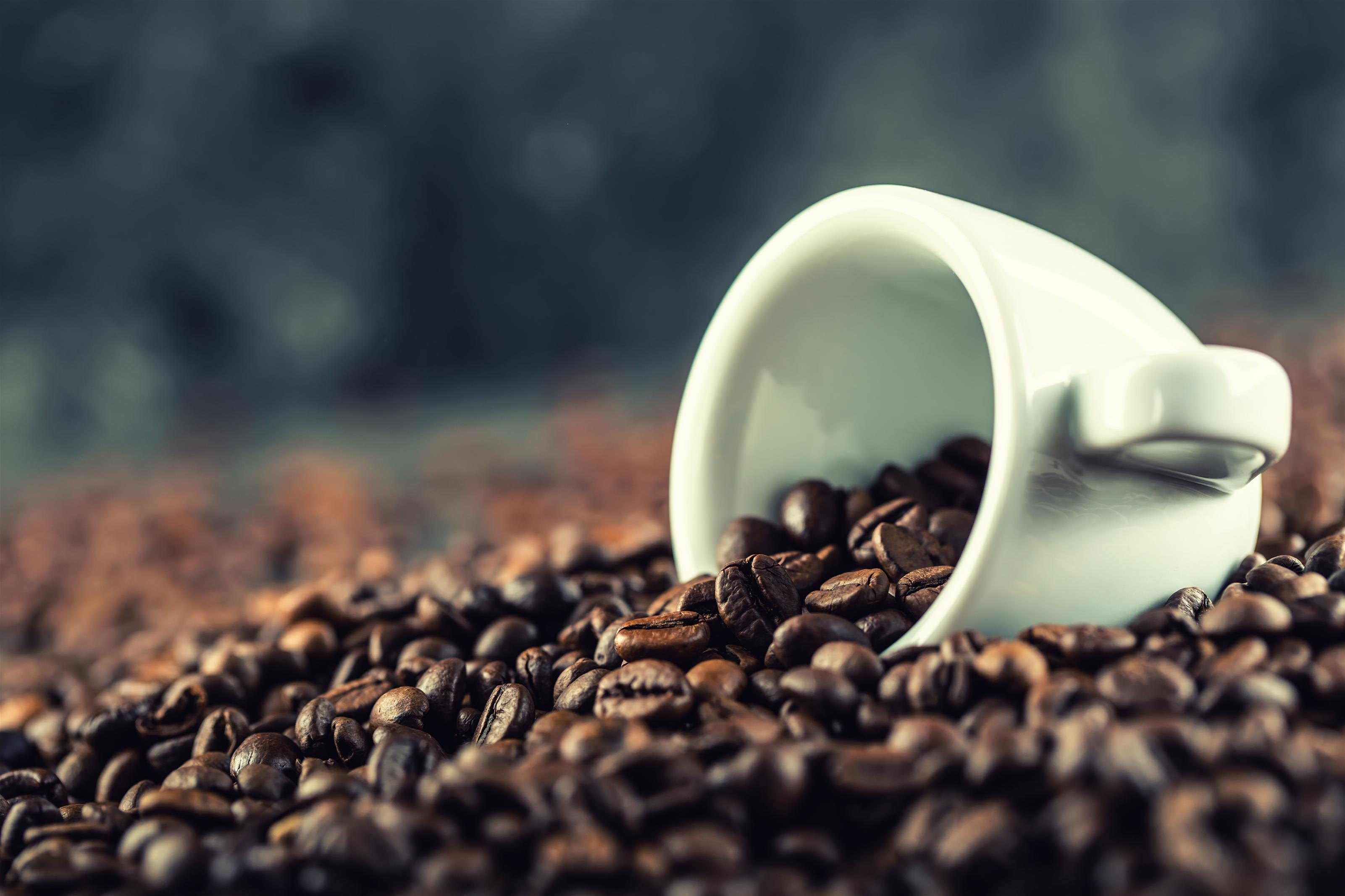 espresso cup and a pile of coffee beans