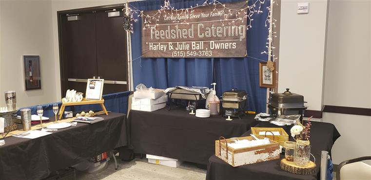 feedshed catering sign above tables with catering supplies
