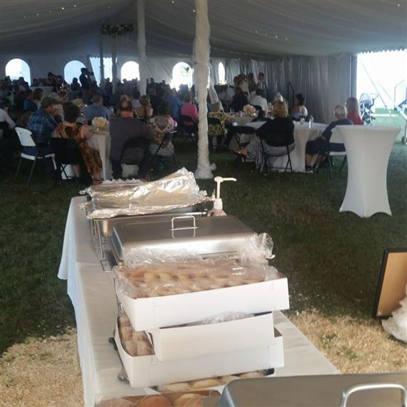 tent with catering trays and people sitting at tables
