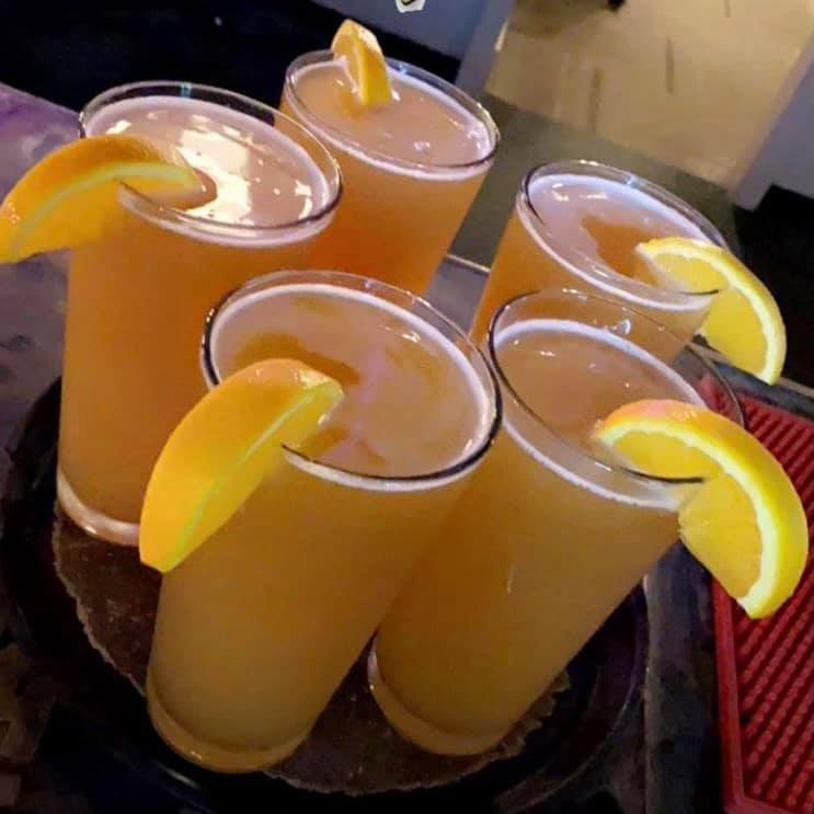5 mimosas with lemons on a tray