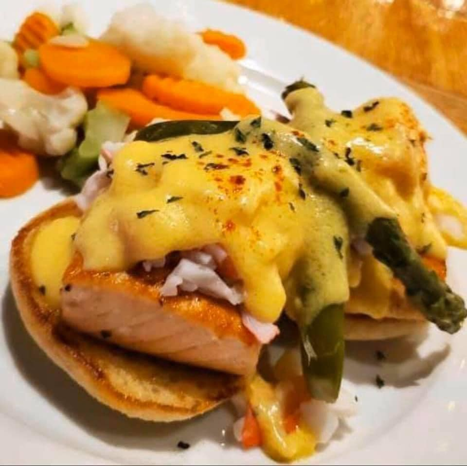 salmon on bread with asparagus and cheese on top and veggies on the side