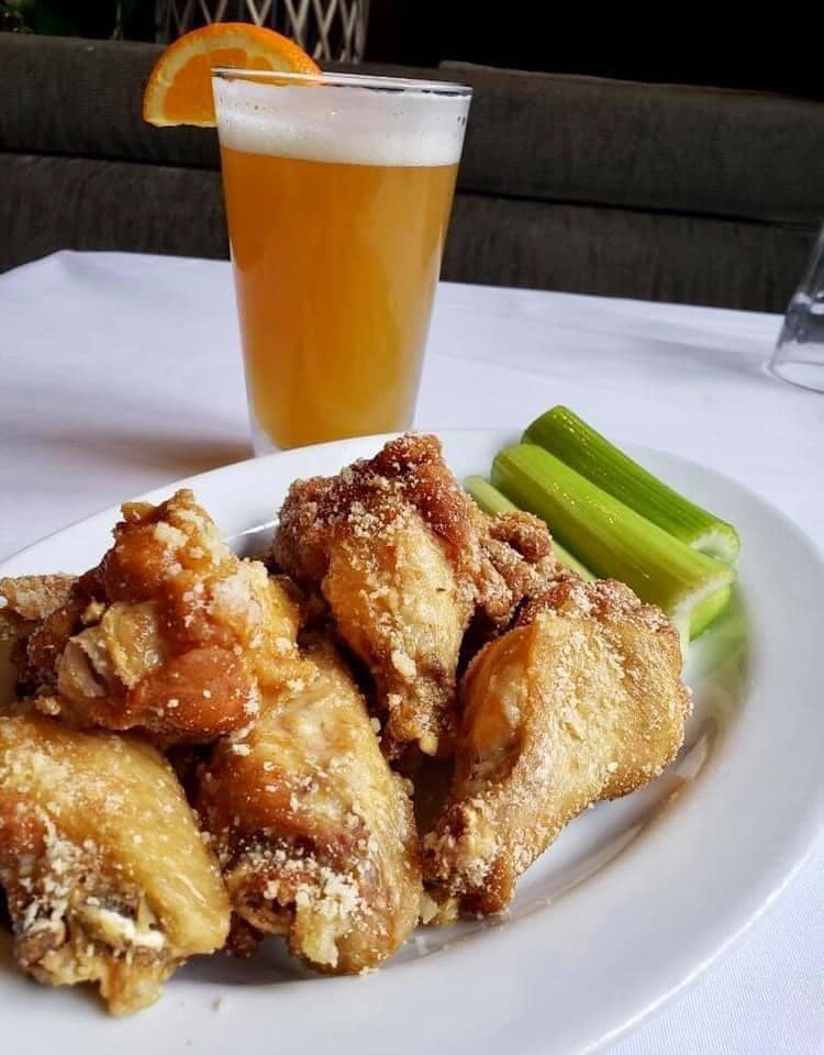 wings with celery and a beer on a table