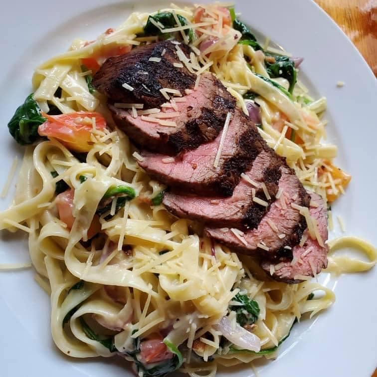 spaghetti with vegetables, cheese, and sliced meat