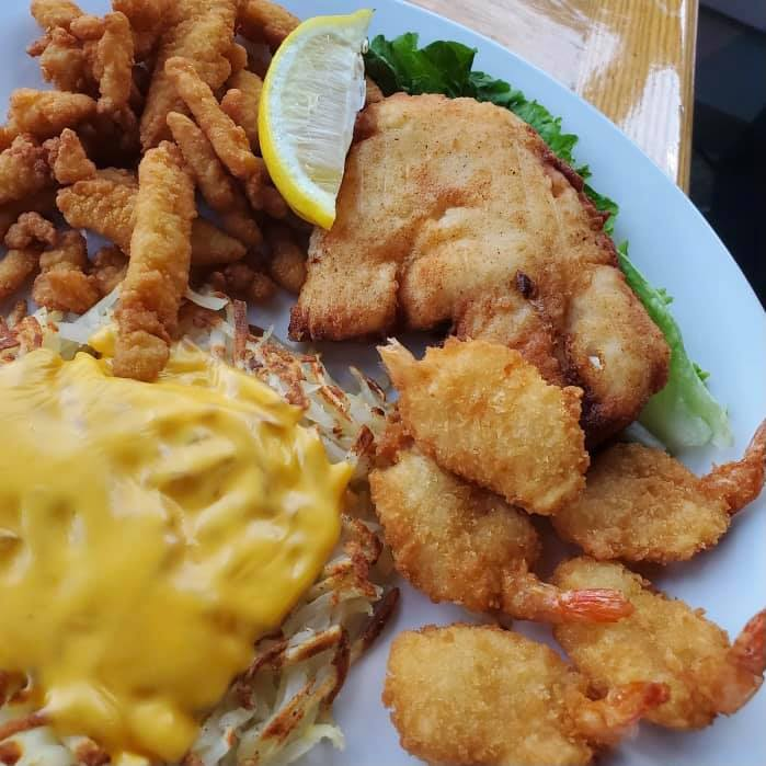 cod, fried shrimp, and hashbrowns with cheese on top