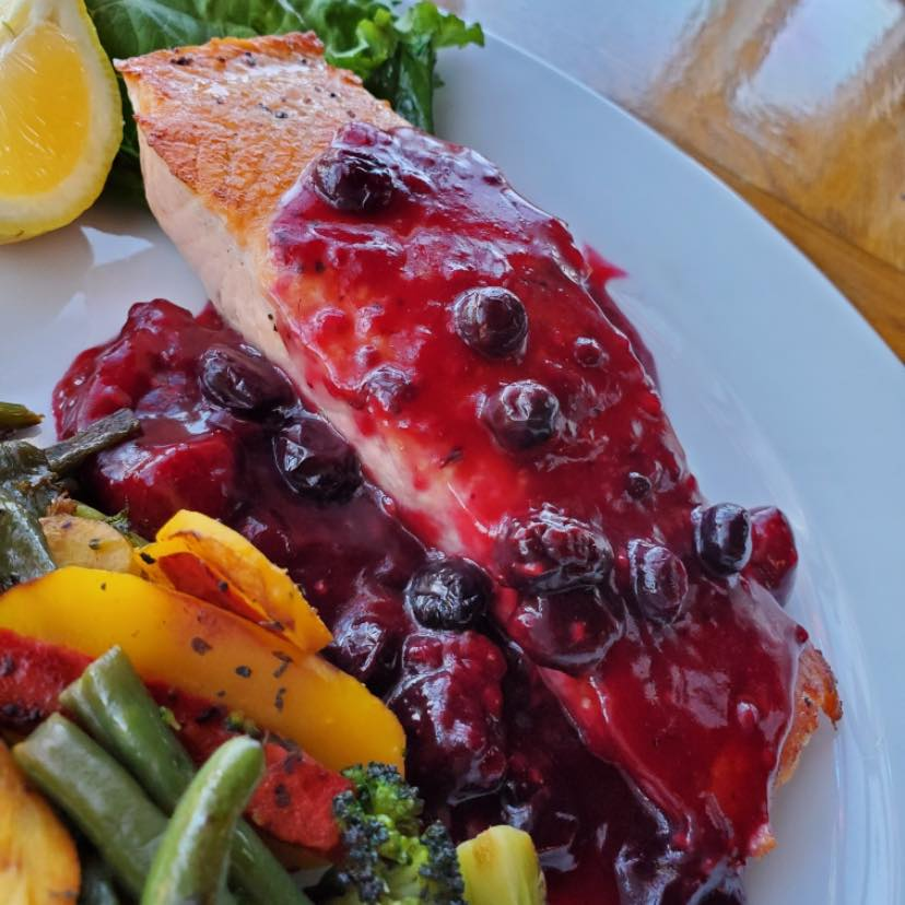 salmon with a blueberry sauce on top and mixed veggies on the side