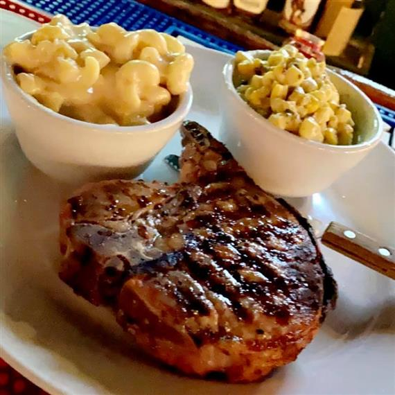 16 oz porterhouse pork chop with sides of white cheddar mac 'n cheese and jalapeno creamed corn