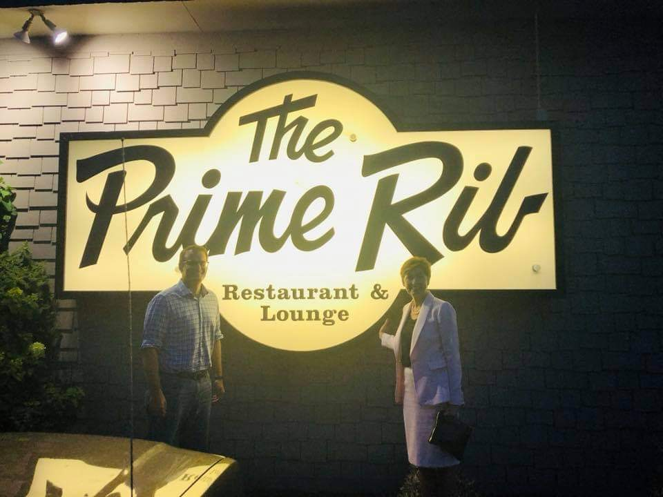 men smiling in front of the prime rib sign