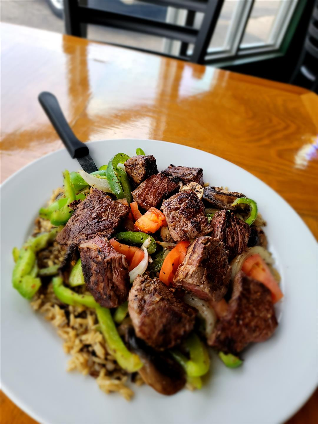 sirloin steak skillet - cut up pieces of steak with peppers and onions on a bed of rice
