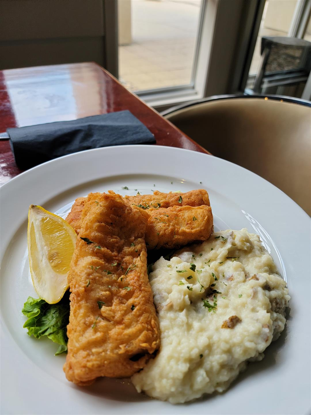 Cod Dinner - two pieces of fried cod with a side of mashed potatoes and a lemon garnish