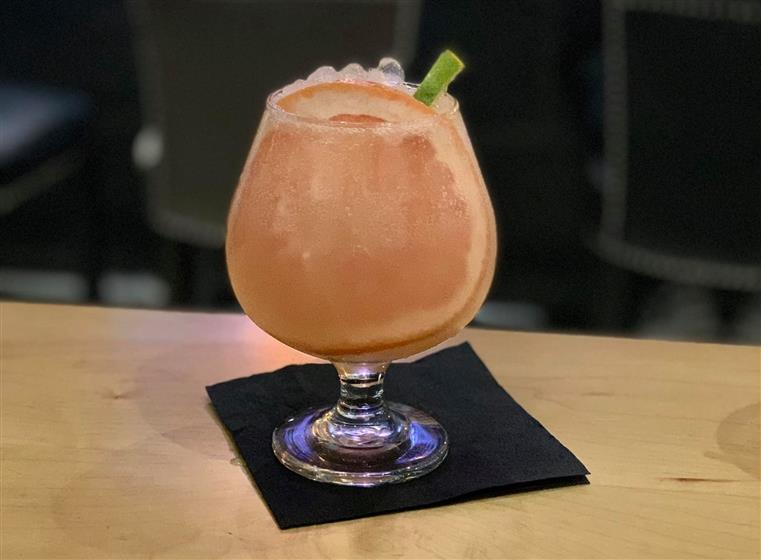 fruity cocktail on the rocks with an orange slice