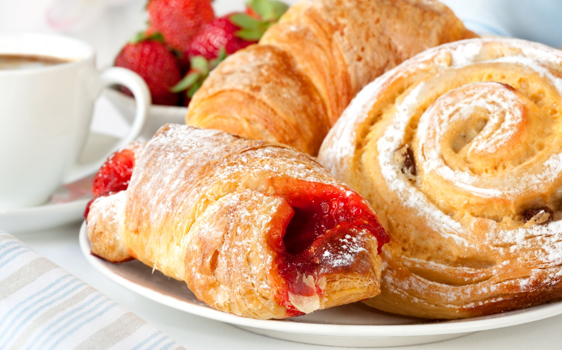 Assortement of breakfast pastries on a plate with a cup of coffee
