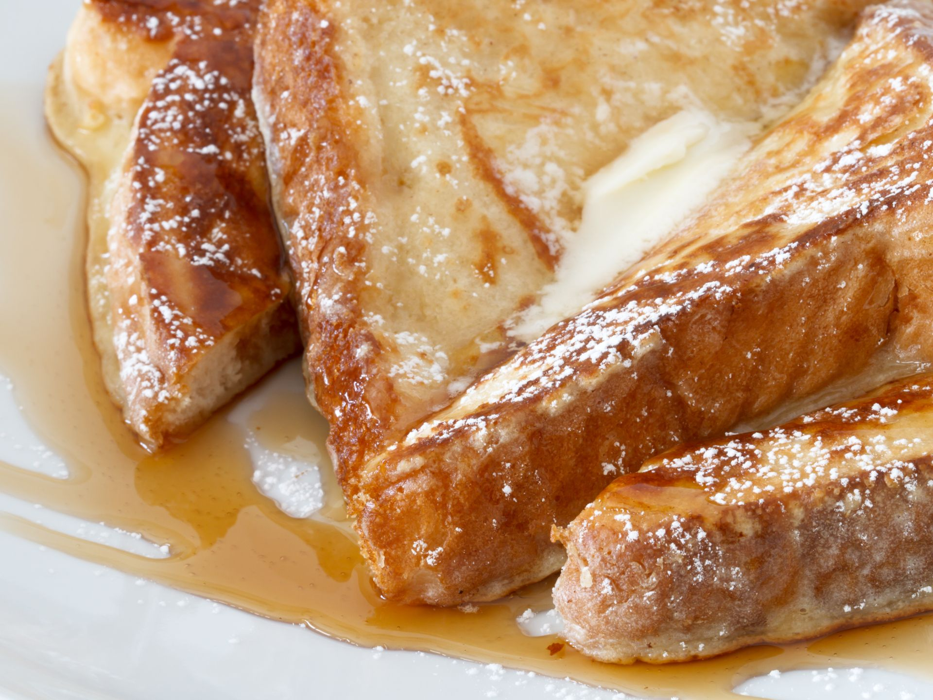 French toast sliced with butter and maple syrup