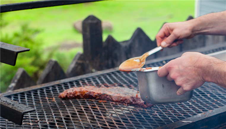 person putting sauce on ribs on the grill