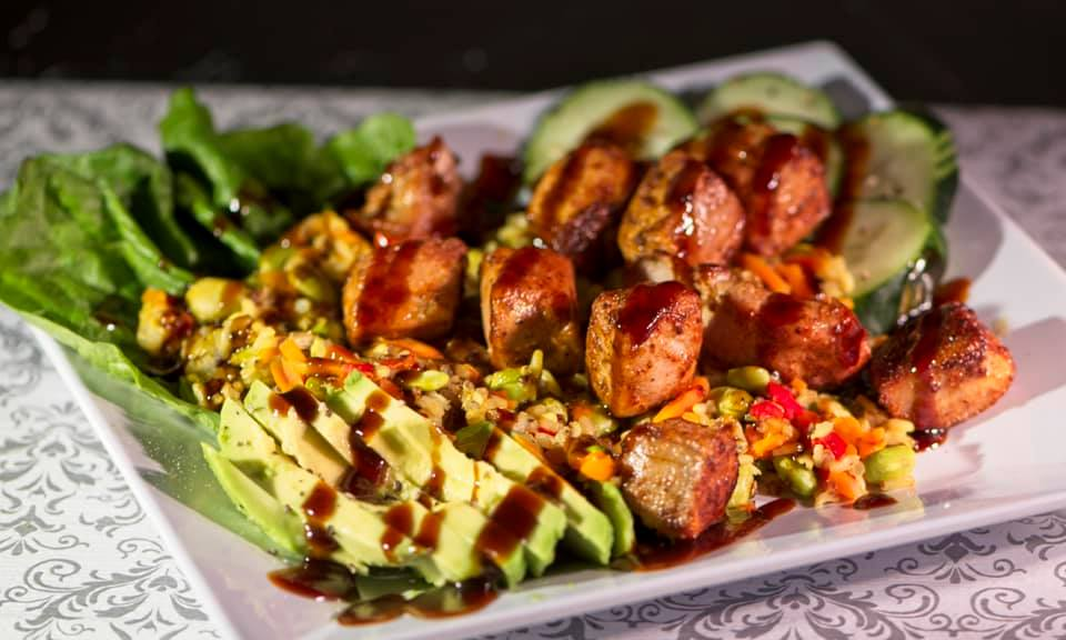 sliced avocado, with roasted potatoes on a bed of lettuce topped with cucumbers