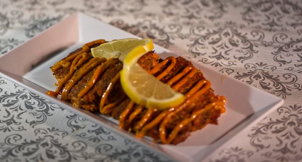 grilled fish topped with sauce and a lemon wedge