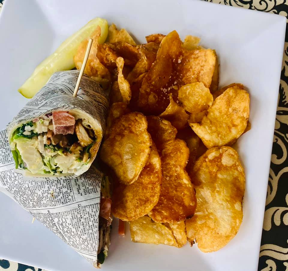 chicken, lettuce, and tomato wrap with a side of potato chips