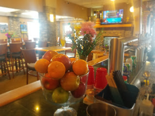 fruit in a bowl and flowers on the bar