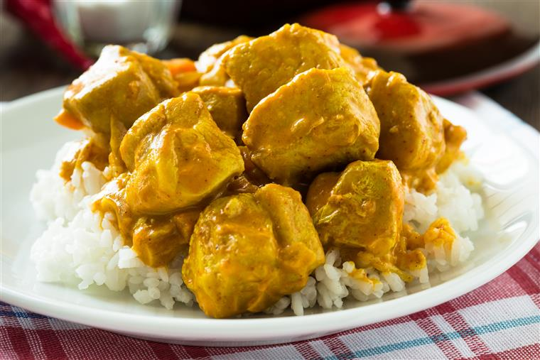 chicken curry on top of white rice on a white plate