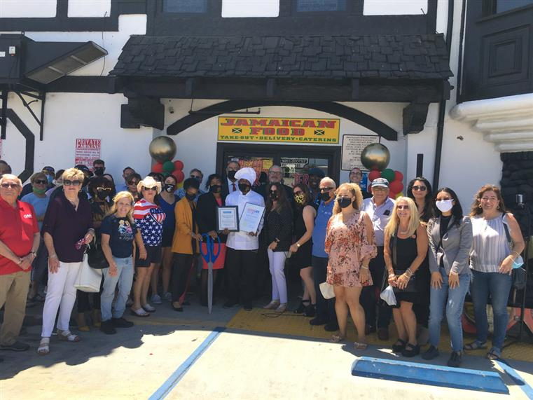 group of people in front of jamaican food sign