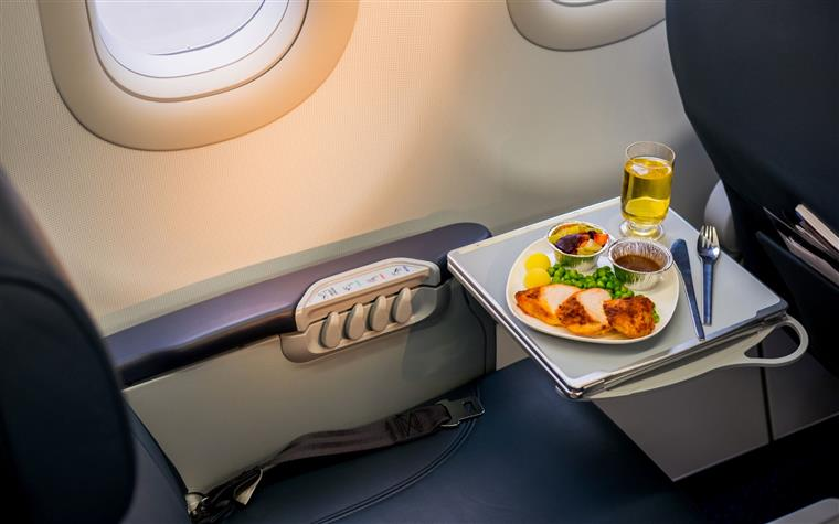 meal served on board of airplane on the table with sliced chicken breast, vegetables and a drink in a glass