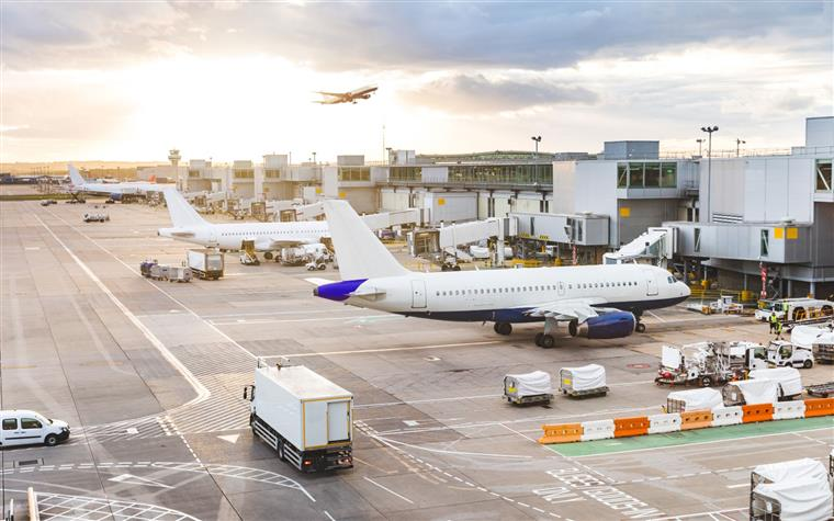 Busy airport view with airplanes and service vehicles at sunset.