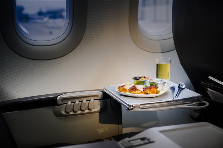 meal served on board of airplane on the table and a drink in a glass