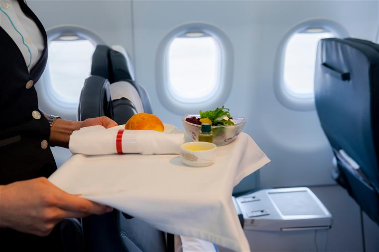 airline attendant with food on a tray