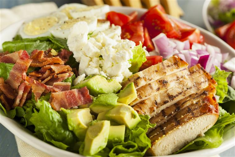 Cobb salad in a bowl with sliced grilled chicken, bacon, avocado, hard boiled eggs, feta and tomatoes
