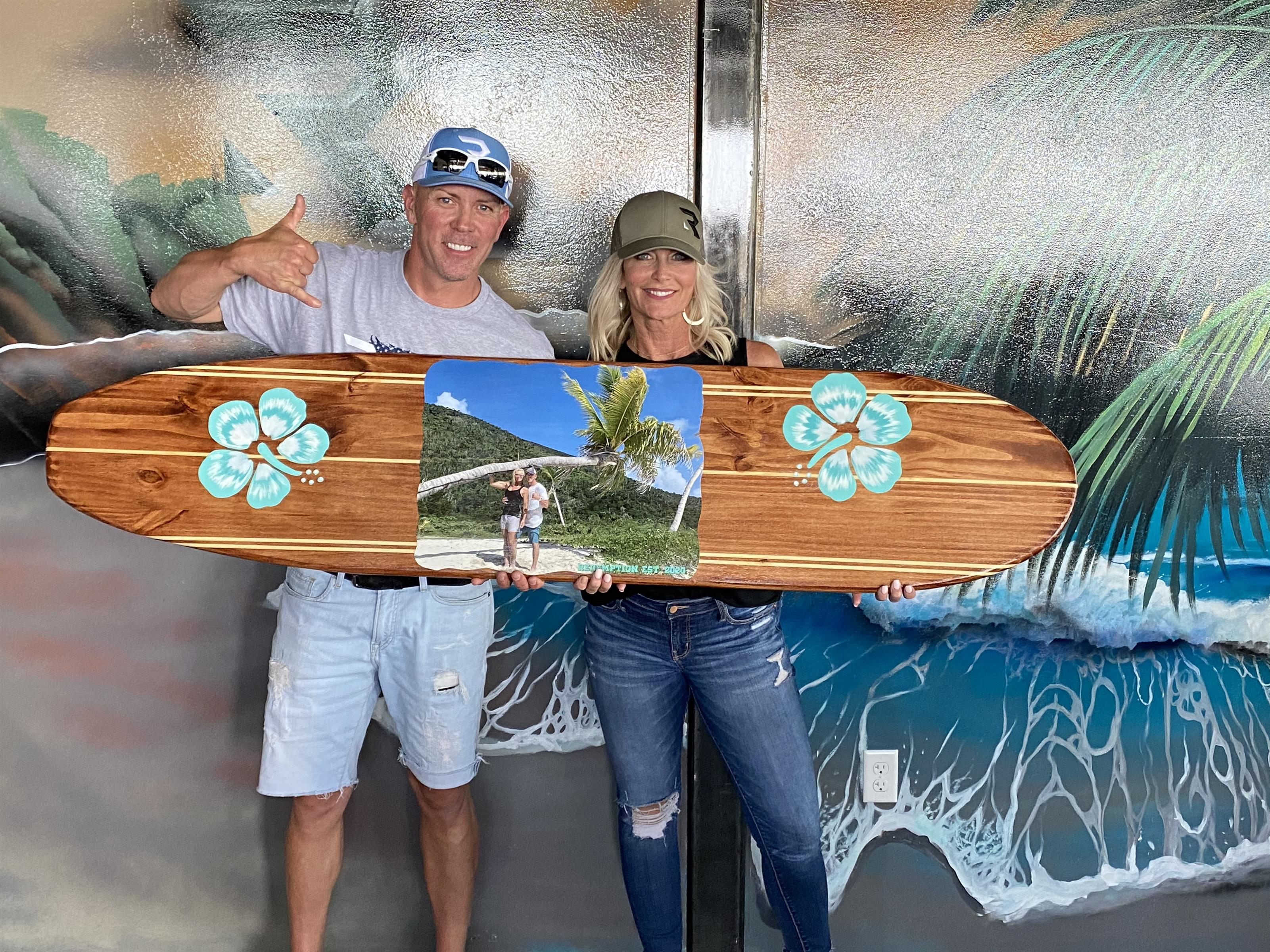 Owners and staff with Surfboard and photo of island