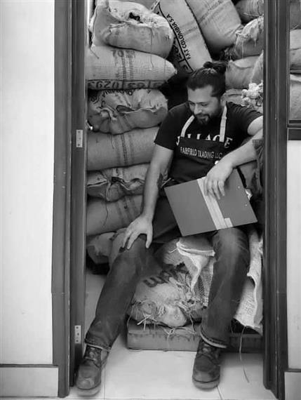 a man with a clipboard sitting on bags of coffee