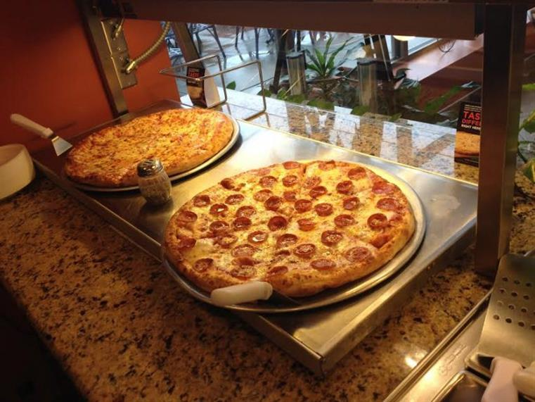 pizza pies displayed on pans