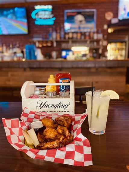 wings in a basket next to a condiment tray and mixed drink