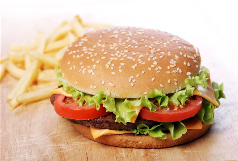 burger with cheese, lettuce, tomato and fries on the side