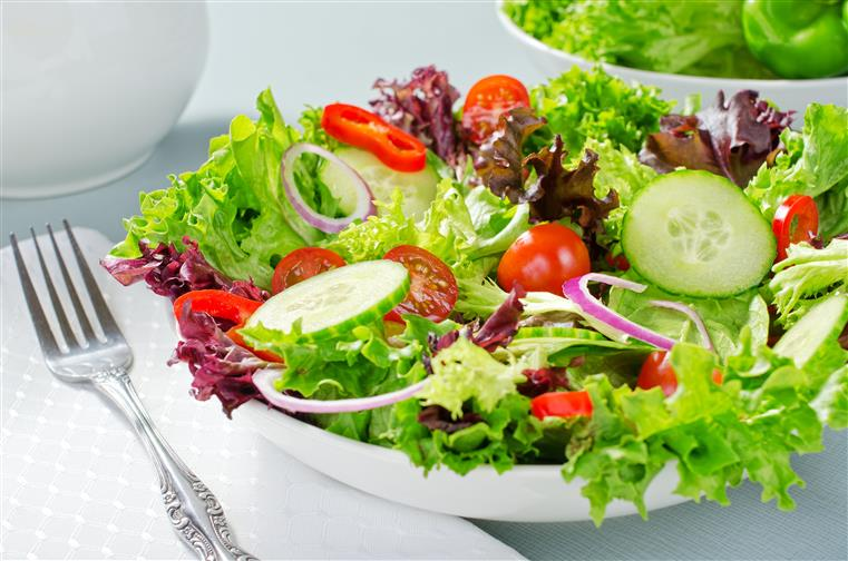 garden salad topped with tomatoes, cucumbers, and red onions