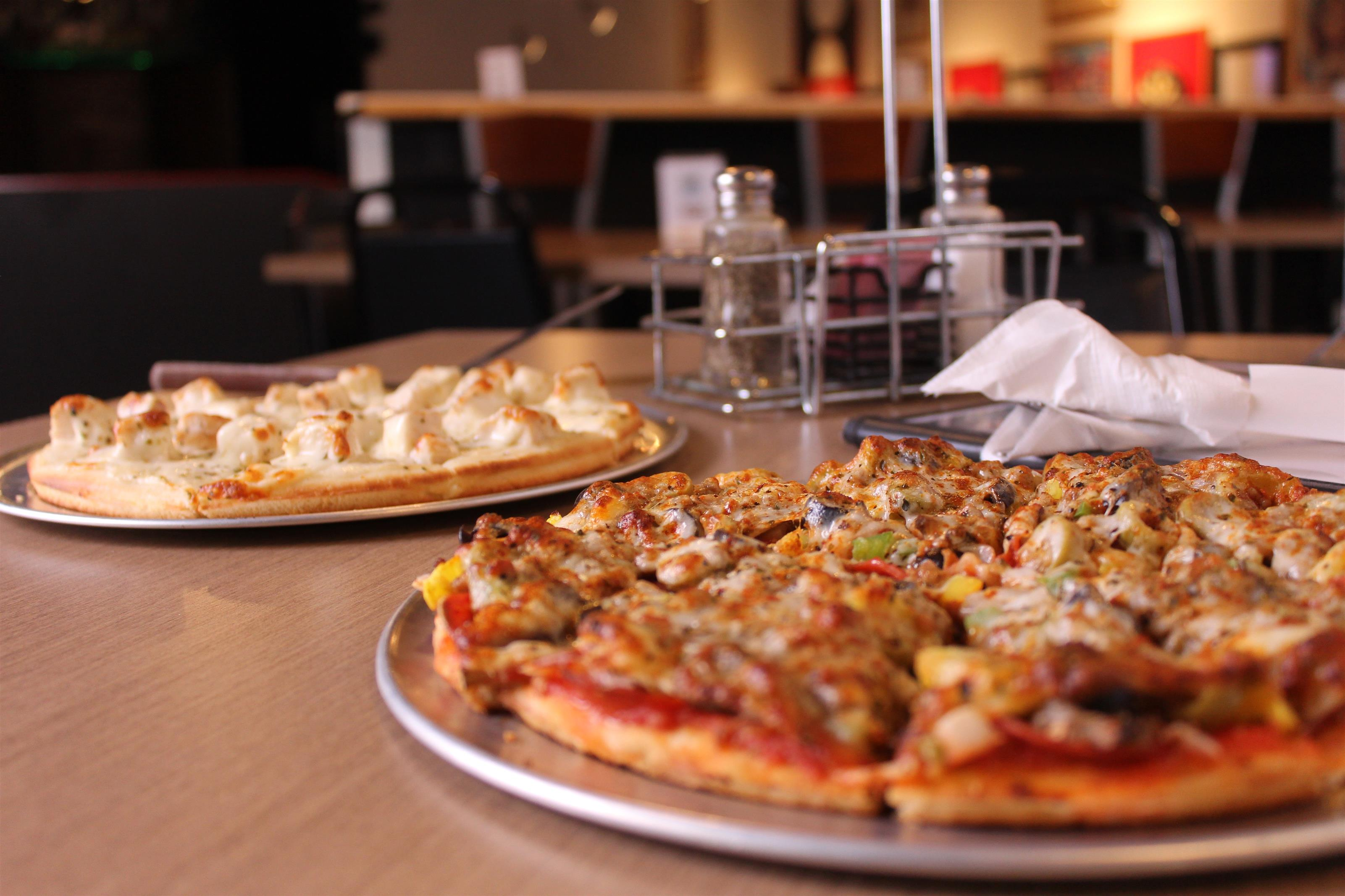 two pizza pies with utensils and menu