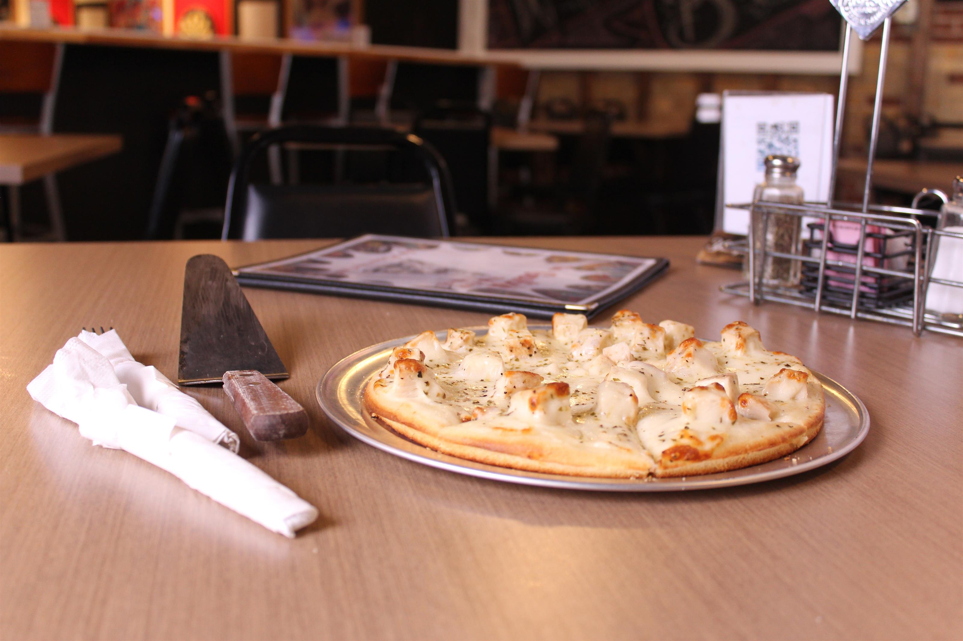 pizza pie with utensils and menu