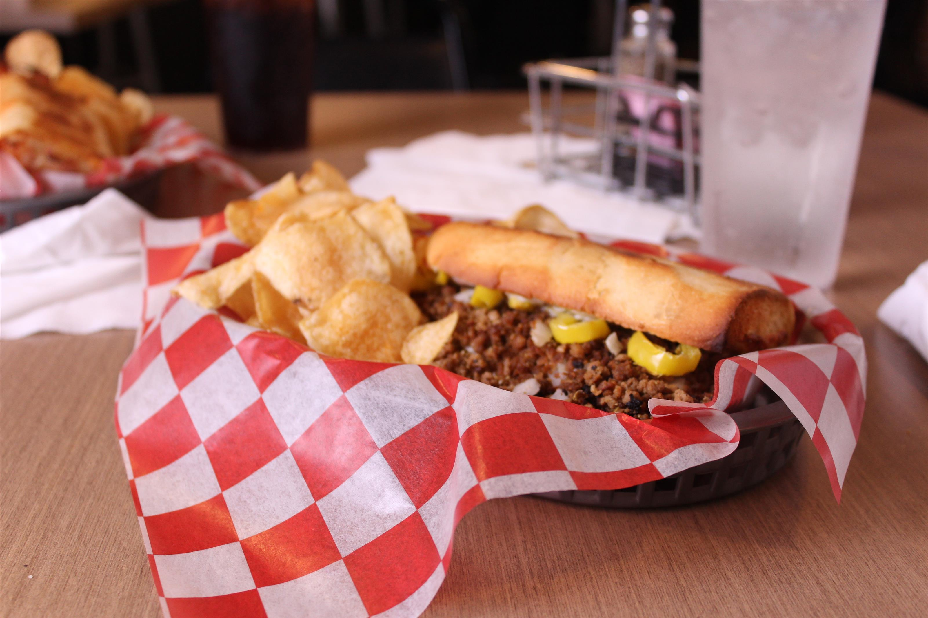 philly cheesesteak with chips in a basket with cola and water
