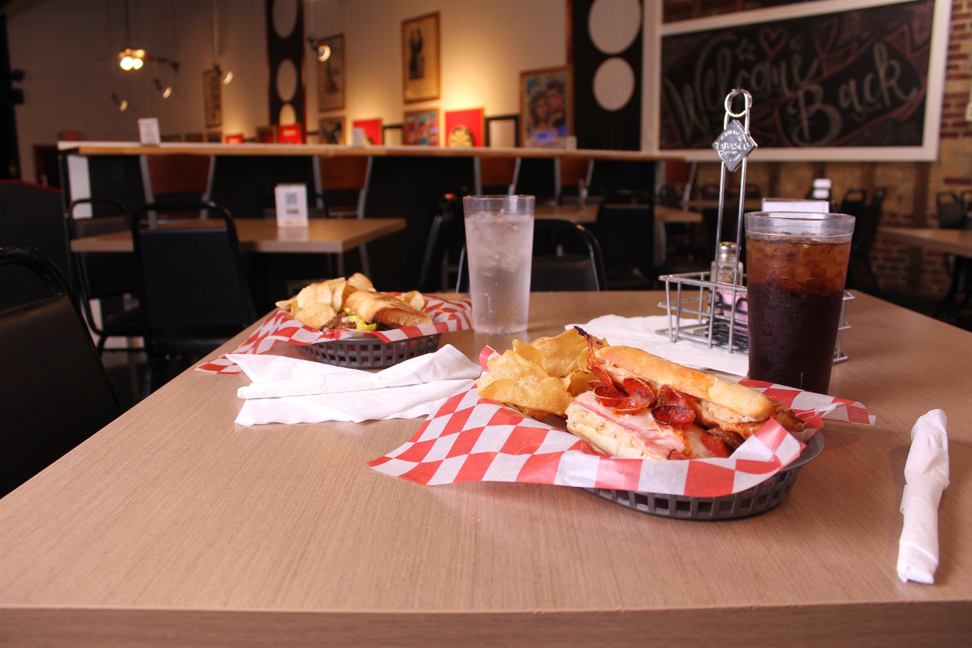 pepperoni hero with chips in a basket with cola and water