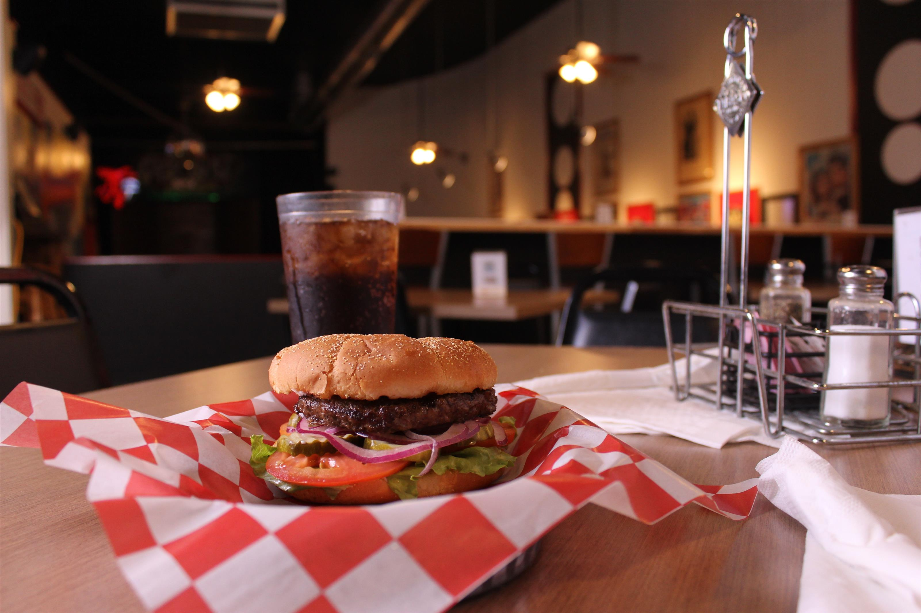 hamburger with cola in background